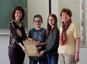 Sandra Mummert und Angelika Wallner (außen) überreichen Lana Steinbrück und Phil Heimhold stellvertretend die Urkunde als Dankeschön für die Spende.