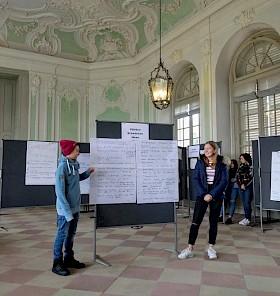 Levin (Privatgymnasium) und Lotta (Hebelgymnasium) präsentieren die Ergebnisse ihrer Gruppe im Schlussplenum.