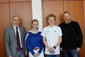 Schulleiter Stefan Ade (links) und Sportfachleiter Carsten Abbe (rechts) gratulieren den neu ausgebildeten Sportmentoren Hannah Gieser und Felix Abbe