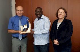 Pastor Frank Tibagendeka aus Uganda übergibt ein Gastgeschenk an Schulleiter Stefan Ade, daneben Pfarrerin Silke Schnepf.