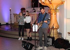 Religionslehrer Bernard Woodley an der Gitarre begleitete den Gesang von Zoe Schwarz und Lyah Fitterer.