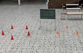 Mit Hütchen werden die Abstandsregeln in der Aula verdeutlicht.