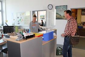 Sekretärin Corinna Bode empfängt Lehrer Markus Herrmann hinter Plexiglas.