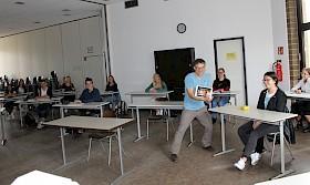 """Mittendrin und virtuell dabei: Religionslehrer Henning Hupe freut sich, dass Prof. Andreas Löschel  (""""auf dem Tablet"""") im Oberstufenkurs online über aktuelle Klima-Fragen referierte."""